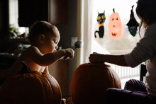 Two Kids Pumpkin Carving At Halloween In Their Home