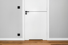 A White Door With A Ventilation Undercut With A Matte Black Handle And A Black Line In The Middle In A Modern House With Vinyl Panels On The Floor.