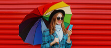 Autumn Portrait Of Happy Young Woman Calling On Smartphone With Colorful Umbrella Wearing A Blue Checkered Coat On Red Background