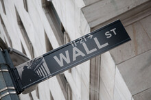 Low Angle View Of Street Sign Wall Street On Road In Manhattan
