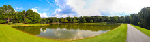 A Stunning Panoramic Shot Of Vast Silky Green Lake Water Surrounded By Lush Green Trees With Mallard Ducks And Geese And Blue Sky And Clouds At Huddleston Pond Park In Peachtree City, Georgia