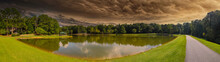 A Stunning Panoramic Shot Of Vast Silky Green Lake Water Surrounded By Lush Green Trees With Mallard Ducks And Geese And Powerful Clouds In The Sky At Huddleston Pond Park In Peachtree City, Georgia