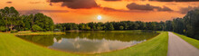 A Stunning Panoramic Shot Of Vast Silky Green Lake Water Surrounded By Lush Green Trees With Mallard Ducks And Geese And Powerful Clouds At Sunset At Huddleston Pond Park In Peachtree City, Georgia