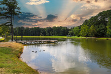 A Gorgeous Shot Of The Still Green Lake Water With Lush Green Trees Reflecting Off The Lake, A Wooden Dock With Black Rod Iron Railing, Ducks And Geese With Blue Sky And Clouds At Huddleston Pond Park