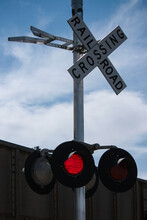 Railroad Crossing Sign In Front Of Cloudy Sky With Red Light Flashing