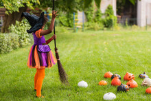 African American Kid In Witch Halloween Costume Holding Broom Near Carved Pumpkins On Lawn