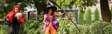 Cheerful African American Kids In Halloween Costumes Holding Brooms Outside, Banner