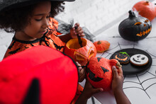 African American Girl Drawing On Pumpkin Of Blurred Brother