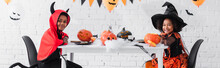 Happy African American Kids In Halloween Costumes Sitting At Table With Pumpkins And Decoration, Banner