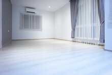 Empty Room Or Bedroom At Night. Interior Inside House Consist Of Wooden Laminate Floor, White Gray Wall, Air Conditioner, Curtain And Adjusting Vertical Blinds. New Clean Look Modern For Background.