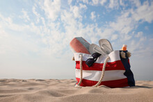 Beach Bag With Flip Flops, Towel, Sunglasses And Sunscreen On Sand, Space For Text