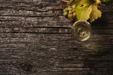 White Wine In A Glass, Grapes And Grape Branches On The Table.