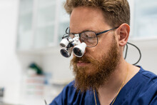 Doctor Operating With Magnifying Glasses