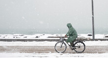 Man Rides A Bicycle In A Snowfall In A Sea Side Road