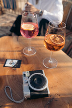 Camera With Picture And Glasses Of Drink On Table