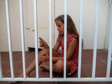 Cute Teenage Caucasian Girl Sitting On The Floor Behind The Bars And Scrolling The Phone