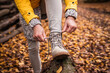 canvas print picture - Woman tying shoelace on her hiking boot. Tourist is getting ready for autumn hike at forest trekking trail