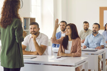Smiling Young Woman From Student Audience Raises Hand To Ask Teacher A Question. Group Of Adult People Listening To Business Trainer Sitting At Tables In Classroom During Corporate Training Or Seminar