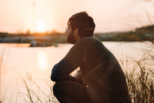 Portrait Of A Bearded Indian Man Sitting Besides The Lake And Looking Sideways