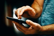 Primer Plano De La Mano De Un Hombre Sosteniendo Su Smartphone. Enviando Un Sms Y Compartiendo Contenidos En Las Redes Sociales Desde El Interior De La Vivienda