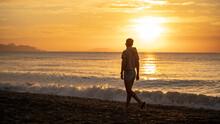 Happy Carefree Woman Enjoying Beautiful Sunrise On The Beach. Yellow Sun Over Sea. Orange Colors Waves. Nature Background. Beautiful Serene Scene. Morning.