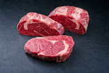 Raw dry aged wagyu rib-eye beef steaks offered as close-up on a black board with copy space