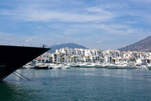 The Foreground Of A Larger Yacht Is Visible In The Foreground. In The Background You Can See The Port Of Puerto Banús And The Mountains Around Marbella.