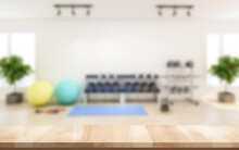 Empty Wooden Table With Blur Modern Gym Interior With Sport Fitness Equipment