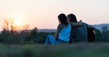 Couple Sits On A Hill And Their Boyfriend Holds A Guitar Singing At Sunset During A Camping Holiday.