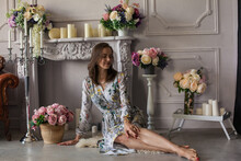 Young Woman With Brown Hair In A Floral Dress Sitting On The Floor Among Many Vases Of Flowers With Different Colors In The White Room. Spring Mood. Portrait Of A Elegant Girl Surrounded By Candles.