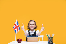 Happy Caucasian Schoolgirl Sitting At The Desk Showing Thumbs Up. English Lesson Great Britain Flag