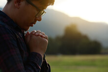 Religious Man Praying To God Resting His Chin On His Hands In A Field During A Beautiful Sunset.His Hands Are Praying For God's Blessings.