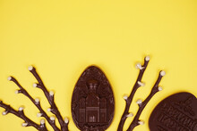 Chocolate Eggs And Chocolate Willow On A Yellow Background. Place For The Test. Postcard Or Banner Concept. Design
