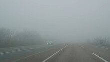 Cars Move On Foggy Road, View Through Windshield In Daytime. Cars Pass Through Fog On Road. Poor Visibility In Mist Highway. Dangerous Weather For Driving. Cars Keep Distance At Haze