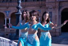 Three Middle-aged Hispanic Women, Wearing Turquoise Costumes And Rhinestones, To Belly Dance. Belly Dance Concept.