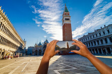 Tourist Hands With A Smartphone Taking Pictures Of San Marco Square In Venice, Italy.