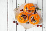 Stuffed mini pumpkins with rice, cranberries, cabbage and nuts. Autumn food concept. Top view on plate over a white wood background.