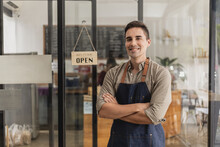 A Male Cafe Employee Standing In Front Of The Store Greets Customers And Has A Sign That Says Open To Show That The Shop Is Open, A Male Employee Opens The Shop To Serve Food And Beverages.