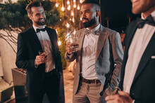 Three Happy Men In Suits Holding Glasses With Whiskey While Spending Time On Party