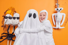 Photo Of Cheerful Small Child Embraces Ghost Has Fun Foolishes Around Poses Against Orange Background Going To Celebrate Halloween. Little Girl Has Playful Mood. International Celebration Concept