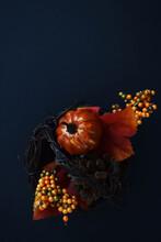 Arreglo Con Una Calabaza Rodeada De Flores Y Hojas Anaranjadas, Verdes Y Amarillas Dentro De Una Canasta Sobre Un Fondo Negro, Representando La Tradición De Halloween Que Se Celebra En Algunos Paises.