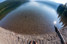 Unique, Fisheye Wide Angle View Of Bowman Lake In Glacier National Park, With Woman's Feet With Sandals On The Shoreline