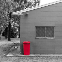 Isolated Red Rubbish Bin Against A Brick Wall