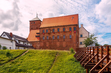 View Of The Gothic Castle Of Pomeranian Dukes In Darłowo. A Moat And A Bridge In The Foreground. The Walls Of The Castle Are Made Of Red Brick And The Roof Is Covered With Tiles