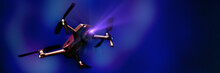 Flying Drone With Camera On Dark Blue Background With Copy Space. Airborne Quadcopter. Also Known As A Drone Or UAV, Unmanned Aerial Vehicle. Low Angle View.