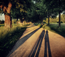 Long Shadows In The Sunset: Two People Silhouettes On The Gravel Of A Country Road