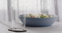 Empty Tumbler Glass On A White Oak Table With Copy Space And Blue Bowl On Background