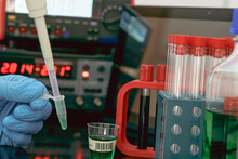 Sample Preparation For Mass Spectrometry In A Scientific Laboratory. Filling Test Tubes With Samples With A Pipette And Measuring Instruments On The Background