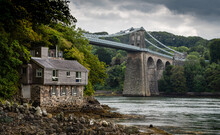 Menai Suspension Bridge In North Wales With Boathouse In Foreground On A Gloomy Day