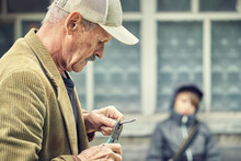 Senior Man Bends Wire With Pliers Grandson Sits On Bench